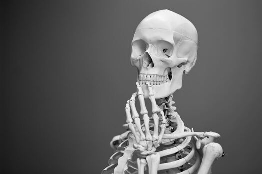 Skeleton with black and grey background thinking
