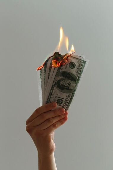 hands holding USD dollar note money burning