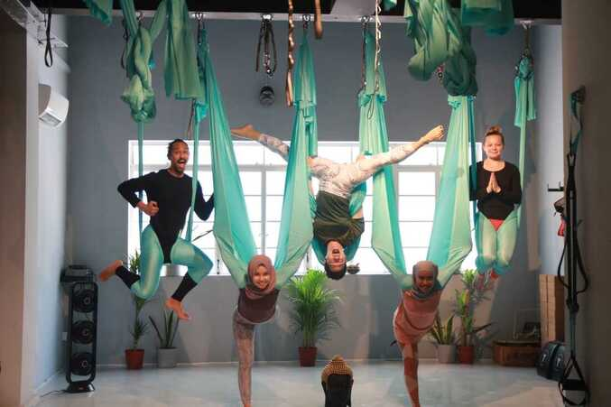 Aerial Fitness in Singapore with five teachers in different pose inside blue hammock